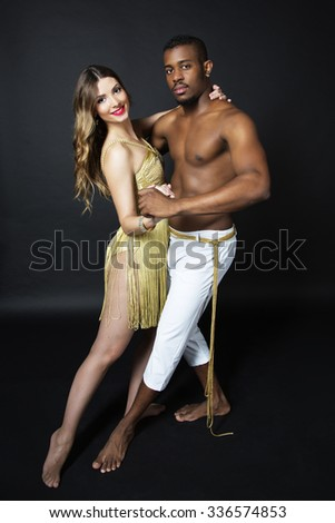 Fashion portrait of attractive dancing couple in sensual hugs. Holding hands. Dancing latino. Passion Love. Sensuality. The girl's perfect skin facial make-up and curly long hair. The guy's pumped abs - stock photo