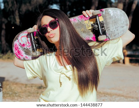 fashion portrait of attractive girl with a skateboard . shot in nature - stock photo