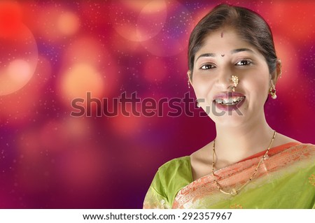 Fashion portrait of beautiful female wearing traditional indian costume, over lighting background - stock photo