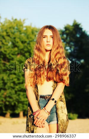 Fashion portrait of beautiful hippie young woman wearing boho chic clothes, chiffon cardigan and boho chic style bijouterie. Blonde haired woman dressed in bohemian style at the beach.  - stock photo
