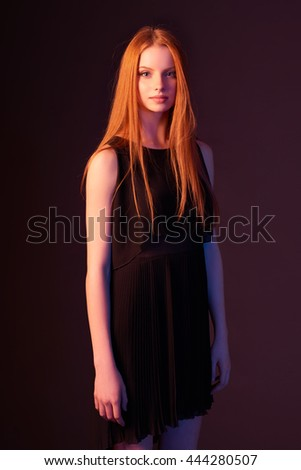 Fashion portrait of beautiful red haired fashion model girl with long hair in black dress, tonned image - stock photo