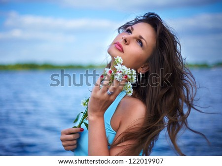fashion portrait of beautiful sexy female brunette girl model lying on the river near the  in blue dress with a flower in his hand and with tears in his eyes - stock photo