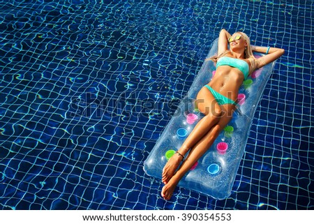 Fashion portrait of beautiful tanned woman with blond hair in elegant bikini relaxing on a swimming pool - stock photo