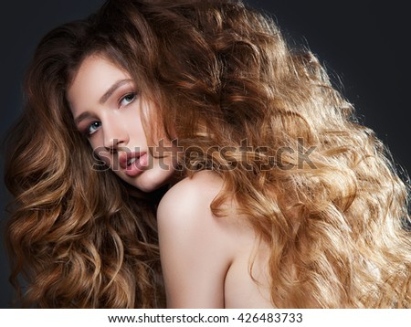 Fashion portrait of beautiful woman with long curly hair. Volume hairstyle. Close up. - stock photo