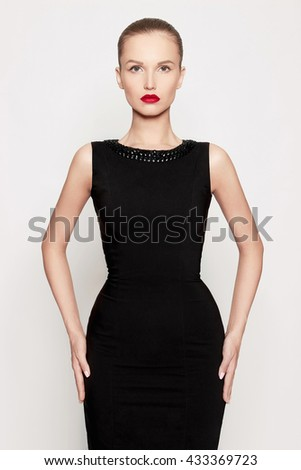 fashion portrait of beautiful young woman in a black dress.beauty sexy girl with red lips - stock photo