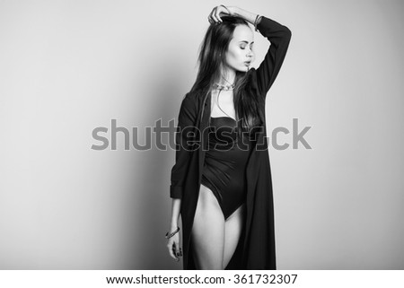 Fashion portrait of beautiful young woman with redhead. Girl in black bodysuit on white background. - stock photo