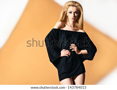 Fashion portrait of beautyful woman in tunic with orange rhomb on background - stock photo