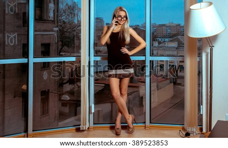 Fashion portrait of cheerful young blonde lady talking phone near the large window. Business woman talking phone. City views behind the window in the office. Business concept. - stock photo