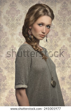 fashion portrait of cute blonde girl with long braid hair-style, gray dress and stylish necklace   - stock photo