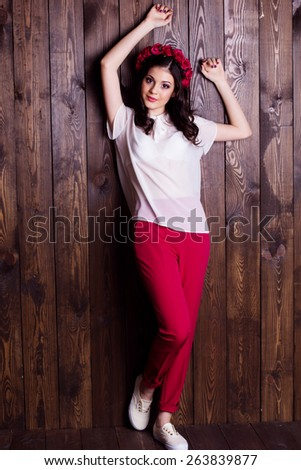 Fashion portrait of cute teenager girl with nice makeup is wearing white blouse and red pants with red roses wreath on her head on wooden background  - stock photo