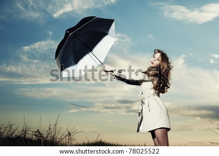 Fashion portrait of elegant woman in a raincoat on the nature. Woman with an umbrella - stock photo