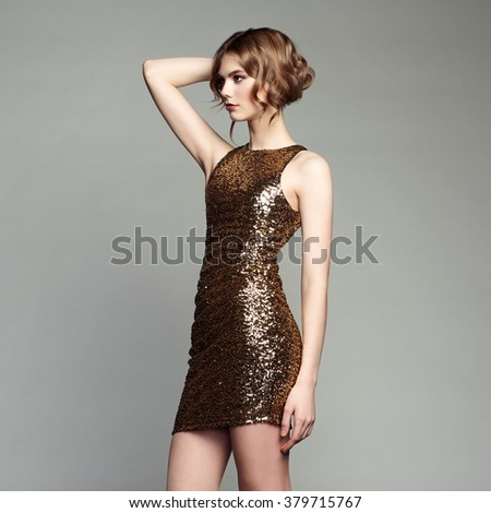 Fashion portrait of elegant woman with magnificent hair. Blonde girl. Perfect make-up. Girl in gold dress on white background - stock photo