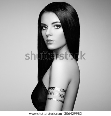 Fashion portrait of elegant woman with magnificent hair. Brunette girl. Perfect make-up. Girl in elegant dress. Flash tattoo gold. Black and white - stock photo