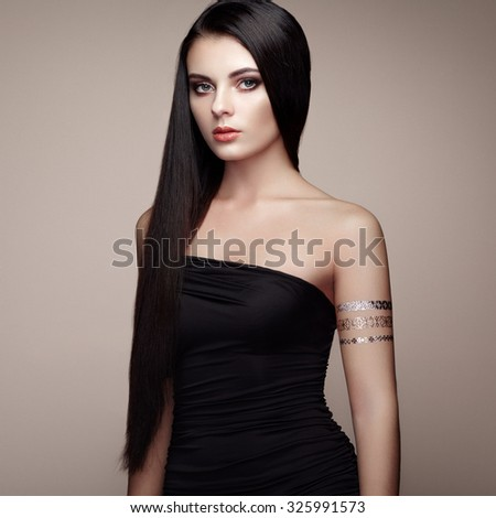 Fashion portrait of elegant woman with magnificent hair. Brunette girl. Perfect make-up. Girl in elegant dress. Flash tattoo gold - stock photo