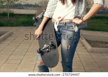Fashion portrait of female holding a skateboard, closeup, instagram color - stock photo