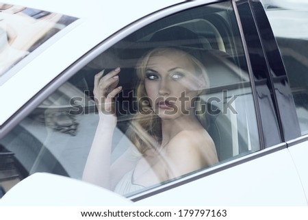 fashion portrait of glamour blonde woman with elegant style and black hat  sitting in a white car  - stock photo