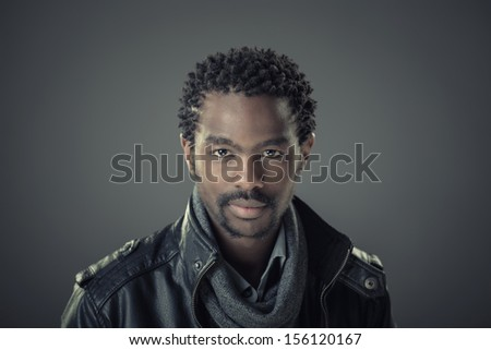 Fashion portrait of handsome, stylish, young african man isolated on grey background with leather jacket - stock photo