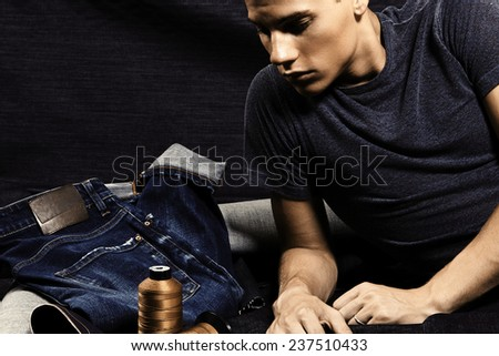 Fashion portrait of handsome young man against denim background - stock photo