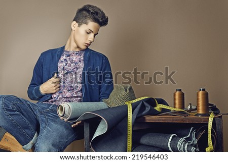 Fashion portrait of handsome young man with tools for sewing denim - stock photo