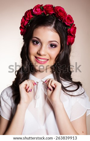 Fashion portrait of happy pretty brunette teenager girl with nice makeup is wearing white blouse and red roses wreath on her head - stock photo