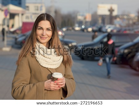 Fashion portrait of happy smiling beautiful girl in a coat and a scarf, standing in the street in spring or autumn. In his hand a cup of hot tea or coffee. - stock photo