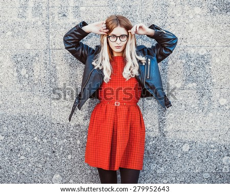 Fashion portrait of hipster woman in stylish casual summer outfit posing against wall background. - stock photo