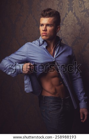 Fashion portrait of man in shirt showing his abs and poses over wall - stock photo