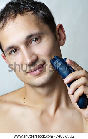 Fashion portrait of man shaved his chin by electric shaver - stock photo