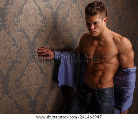 Fashion portrait of man showing his muscular body and poses over wall - stock photo
