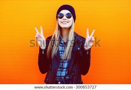 Fashion portrait of pretty blonde girl in trendy black rock style posing having fun over colorful wall - stock photo