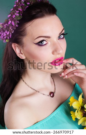 Fashion portrait of pretty girl with purple wreath of flowers in hair and fashion makeup is holding daffodil flowers in hands - stock photo