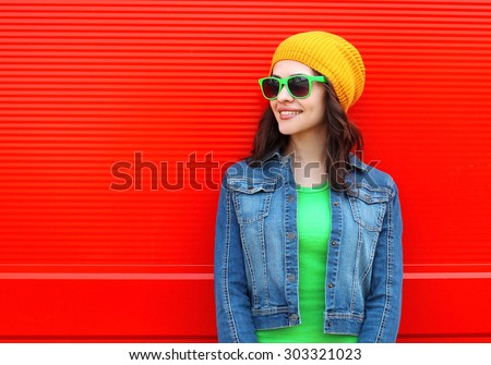 Fashion portrait of pretty young smiling woman wearing a sunglasses and colorful clothes against the red background - stock photo