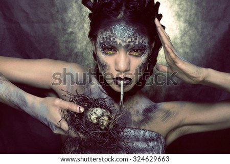 fashion portrait of pretty young woman with creative make up like a snake halloween look - stock photo