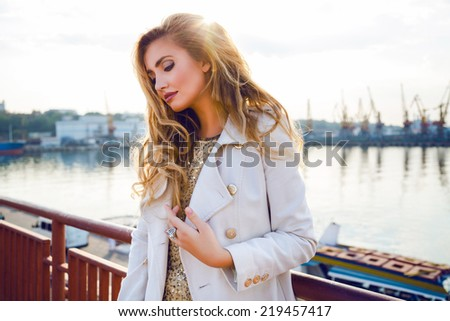 Fashion portrait of sensual sexy woman with perfect elegant hairstyle and natural makeup posing at sea port on sunset, wearing trendy light cashmere coat and golden top, Soft natural colors. - stock photo