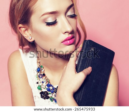 Fashion portrait of sexy beautiful woman with blond hair wearing a white lace top and necklace holding a leather purse and posing on pink background - stock photo