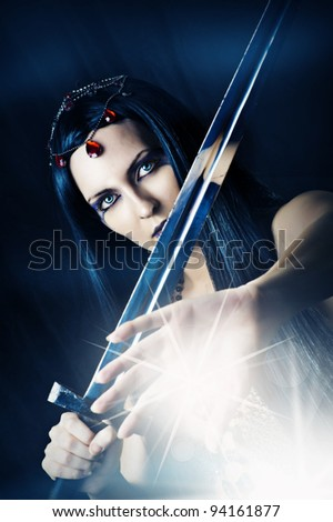 Fashion portrait of sexy brunette woman - witch. She is making magic and holding medieval sword - stock photo