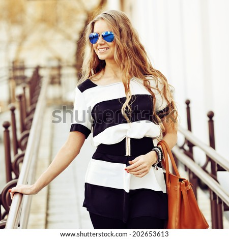 Fashion portrait of smiling young blonde woman with handbag wearing sunglasses - stock photo
