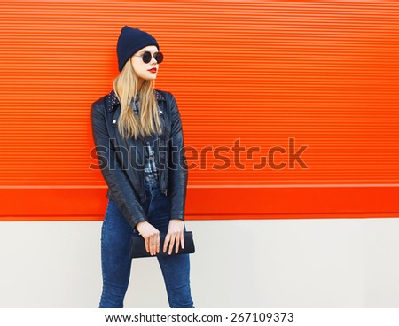 Fashion portrait of stylish blonde girl in rock black style, wearing a sunglasses and leather jacket with clutch standing outdoors against the red urban wall in the city - stock photo