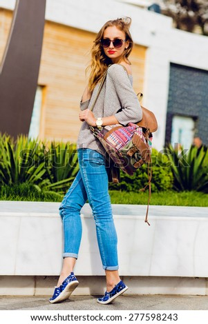 Fashion portrait of stylish   blonde woman in casual spring outfit posing on the street. - stock photo