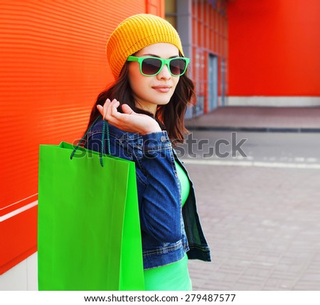 Fashion portrait of stylish cool young girl in sunglasses with shopping bags outdoors  - stock photo