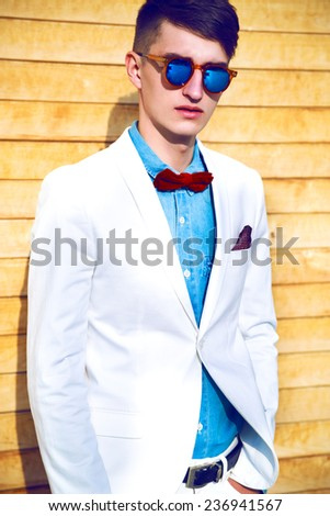 Fashion portrait of stylish man with hipster haircut, wearing trendy elegant white suit, denim shirt, bow tie and mirrored sunglasses, posing near wooden wall.  - stock photo