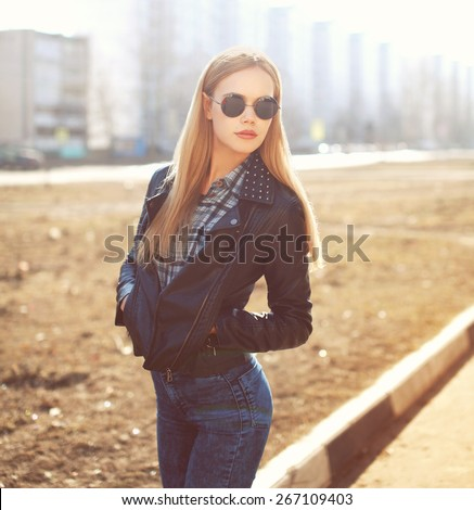 Fashion portrait of stylish pretty blonde woman outdoors in sunny day - stock photo