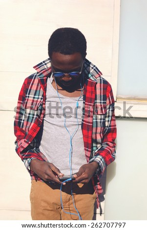 Fashion portrait of stylish young african man standing listens to music on the smartphone, hipster wearing a plaid red shirt and sunglasses against the urban wall outdoors - stock photo