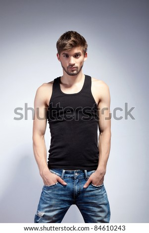Fashion portrait of the young beautiful man in black t-shirt posing over gray background, series photo - stock photo