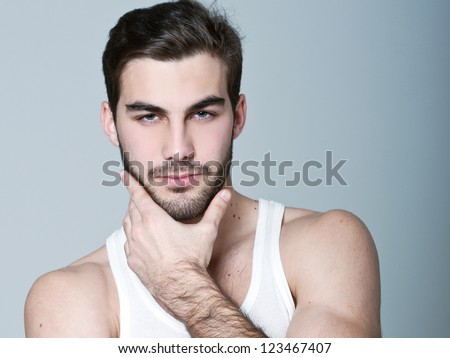 Fashion portrait of the young beautiful man in white t-shirt posing over gray background, series photo - stock photo