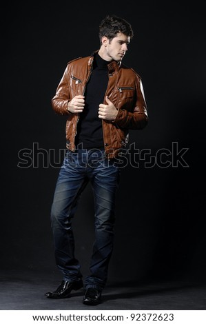 Fashion portrait of the young man on black background - stock photo