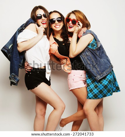 Fashion portrait of three stylish sexy hipster girls best friends, over gray background. Happy time for fun. - stock photo