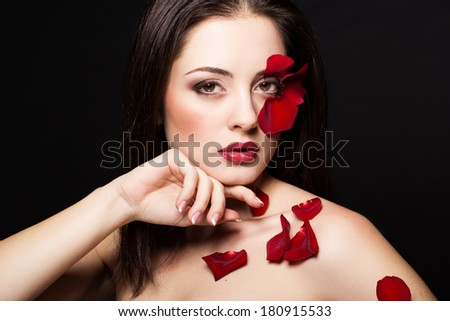 Fashion portrait of woman with rose petals on her face  - stock photo