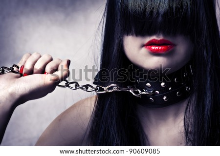 Fashion portrait of young beautiful female model. Glamour woman with long black hair and sexy hairstyle. Lady with leather collar with studs on a metal chain in hand. Red make-up on lips and manicure - stock photo