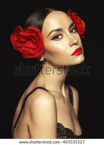 Fashion portrait of young beautiful lady with earring on black background - stock photo